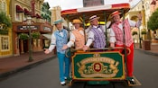The 4 members of the Dapper Dans barbershop quartet pose at the front of a trolley car parked on Main Street USA