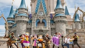 Donald Duck in a winged Viking helmet and a fur vest performs in front of Cinderella Castle with the cast of Tangled