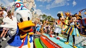 Donald Duck waves to the camera as Mickey and Minnies look on at the Move It! Shake It! Dance & Play It! Street Party