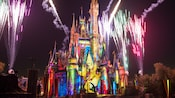 Brilliant colors wash over Cinderella Castle as fireworks light up the sky above
