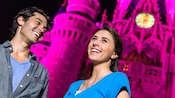 A young male Guest smiles at a female companion as Cinderella Castle stands illuminated behind them