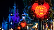 Mickey Mouse-themed pumpkin lanterns glow at night on the streets near Cinderella Castle