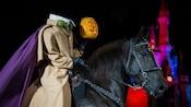 A headless horseman rides a horse and holds a candlelit jack-o'-lantern near Cinderella Castle
