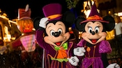Mickey and Minnie wearing vibrant Halloween costumes