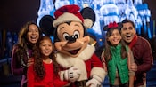 A happy family poses with a Santa-costumed Mickey Mouse as Cinderella Castle illuminates behind them