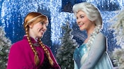 Anna and Elsa smiling at one another, surrounded by the glow of glimmering holiday lights