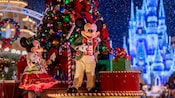 Mickey and Minnie Mouse on a parade float with a richly decorated Christmas tree
