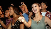 A teenage audience sings and dances in place