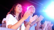A teen girl and a teen boy clap their hands along with an audience