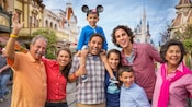 A multigenerational family of grandparents, parents and kids smiles for the camera on Main Street USA