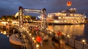 People cross a bridge next to a houseboat styled restaurant identified by a sign as Fultons Crab House