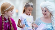 A young female Guest in a 'Frozen' t-shirt and tiara receives autographs from Anna and Elsa at Epcot