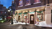 A view at night of the outside of Its Wonderful Shop that includes an outdoor display with decorative snow, a snowman, holiday hats and holiday themed plush toys.