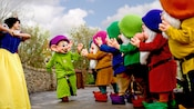 Snow White looks on in glee while Dopey slaps hands with a line-up of the remaining 7 Dwarfs