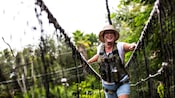 A smiling woman in a straw-hat and wearing a safety harness crosses a rope bridge