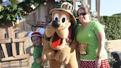 A young girl in Santa style Mickey Mouse ears and a woman in sunglasses pose on either side of Pluto in front of a Christmas themed background