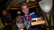 In a beer hall style venue, a man wearing a Donald Duck outfit and a runners medallion around his neck carries a plastic bag in one hand and a cardboard tray with 4 cups of beer in the other