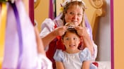 A lady putting a tiara on a girl in a princess costume as they look in the mirror