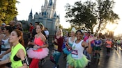 A pack of marathoners dressed in tiaras, tutus and princess themed sportswear smiles and waves as they run past Cinderella's Castle