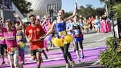 Jubilant marathoners dressed in prince and princess themed sportswear running next to Spaceship Earth attraction in the background