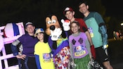 A family of 5 dressed in sportswear pose with Goofy
