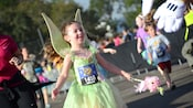 A small girl smiles while dressed in a Tinker Bell costume with a Run Disney Kids Race bib