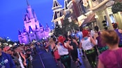 A steady stream of marathoners running past observers on the sidelines toward Cinderella Castle