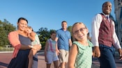 A young girl holds hands with a VIP Tour Guide as he guides her family through Magic Kingdom park