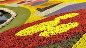 Bright flowers form a Mickey Mouse design in a garden at Epcot International Flower & Garden Festival