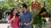 A couple smiles at each other near a topiary display inspired by Disney's Beauty and the Beast