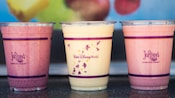 Three refreshing tropical smoothies in plastic cups