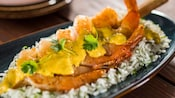Sugar cane shrimp skewer served over steamed rice and topped with coconut lime sauce