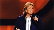 Musician Peter Noone, of the band Herman's Hermits, singing into a microphone