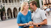A couple enjoys food and wine at an outdoor table in Epcot's Italy Pavilion at Walt Disney World Resort