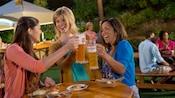 Tres mujeres sentadas en una mesa al aire libre brindan con jarras de cerveza