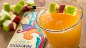 A bright tropical drink sitting directly next to an Epcot International Food & Wine Festival pamphlet