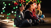 Dots of colorful lights swirling around wide-eyed children sitting crossed-legged