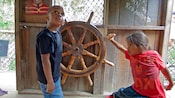 In a pirate themed play area, a boy and young girl each hold one of the handles of a wooden ship's wheel