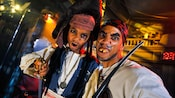Father and son transformed into pirates pose for the camera