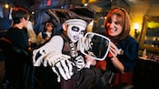 Boy dressed as skeleton ghoul scowls as a Cast Member holds up a mirror for him