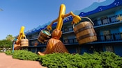 2 versões gigantes dos esfregões dançantes empunhando baldes do Disney's Fantasia decoram a lateral do Disney's All-Star Movies Resort