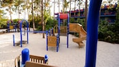 A sandy playground with a climbing apparatus, slide, nets and monkey bars at Disney's All-Star Music Resort