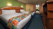 Deux lits doubles avec une table de nuit près d'une porte et une fenêtre, en face d'une commode et d'un téléviseur