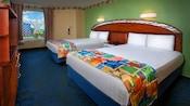 Dos camas dobles con una sola cabecera curvada de madera que abarca ambas camas