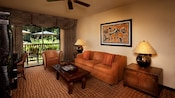 Sofa, wooden coffee table, rattan armchair, African wall art, curtained balcony