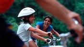 Una niña pequeña sonriente con un casco de seguridad anda en bicicleta mientras su madre la observa felizmente en el fondo