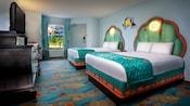 Dos camas dobles con temática submarina frente a un TV/cómoda, mesa y, detrás, una ventana y una puerta de entrada