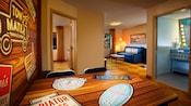 Una mesa con temática de Cars que se transforma en una cama doble, frente a un baño, sala de estar y dormitorio