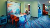 Una mesa con temática del océano que se convierte en una cama doble y, detrás, un dormitorio y una sala de estar