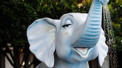 Head of blue baby elephant sculpture with a shower of water flowing out of its trunk